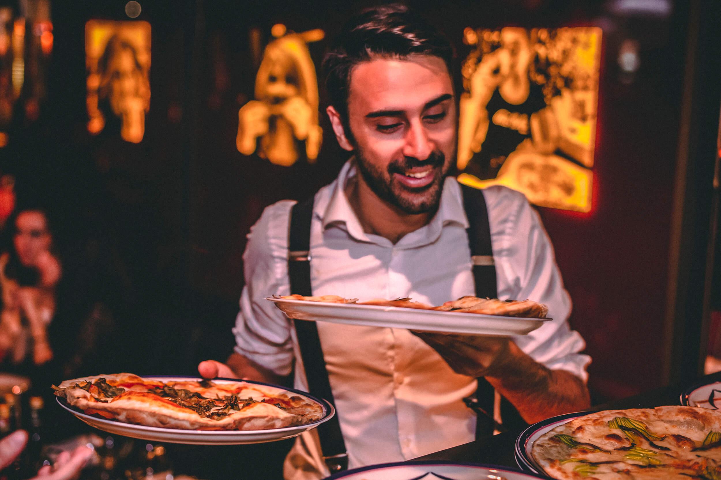 Waiter serving fresh pizza.