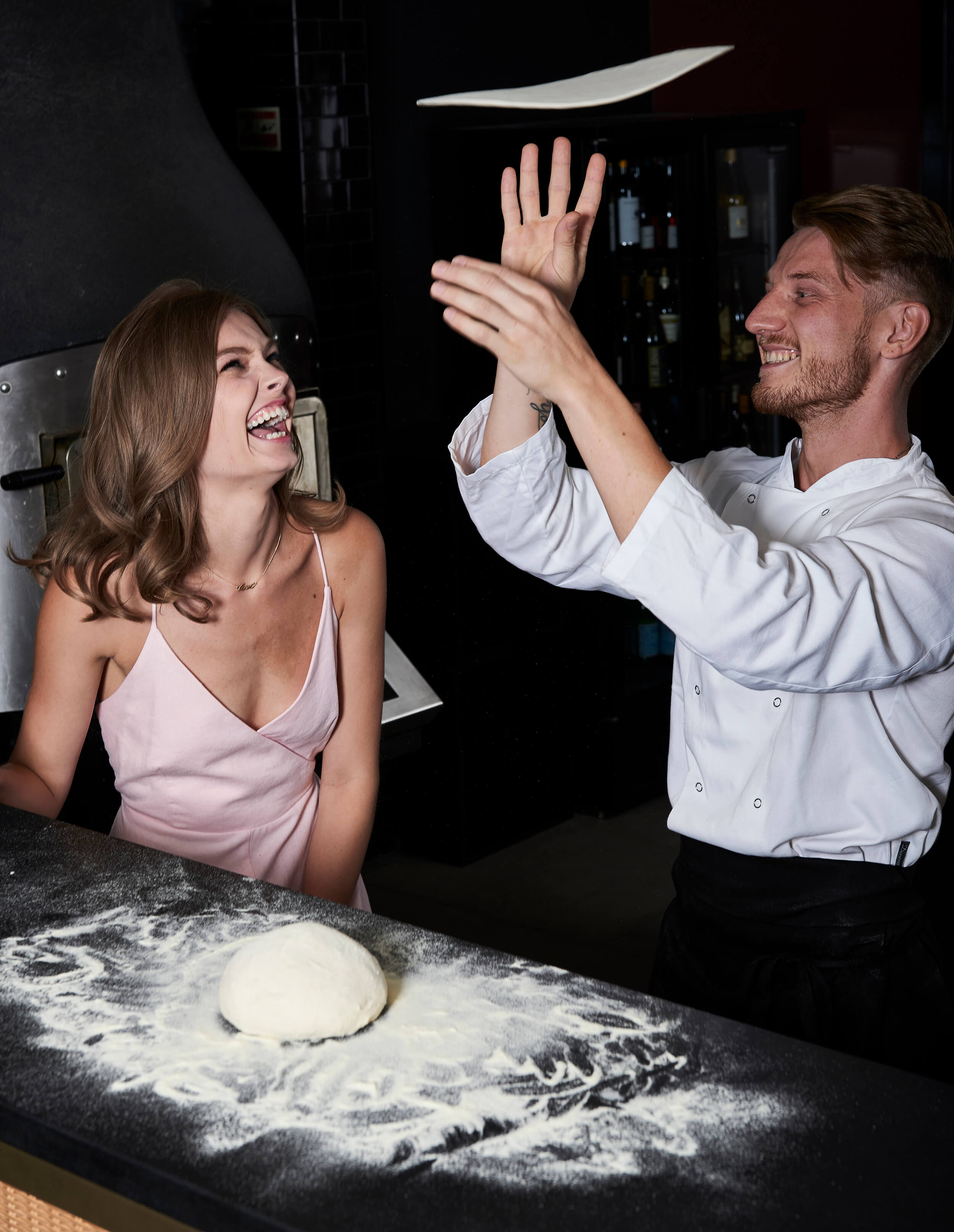 Chef spinning dough while woman is laughing.