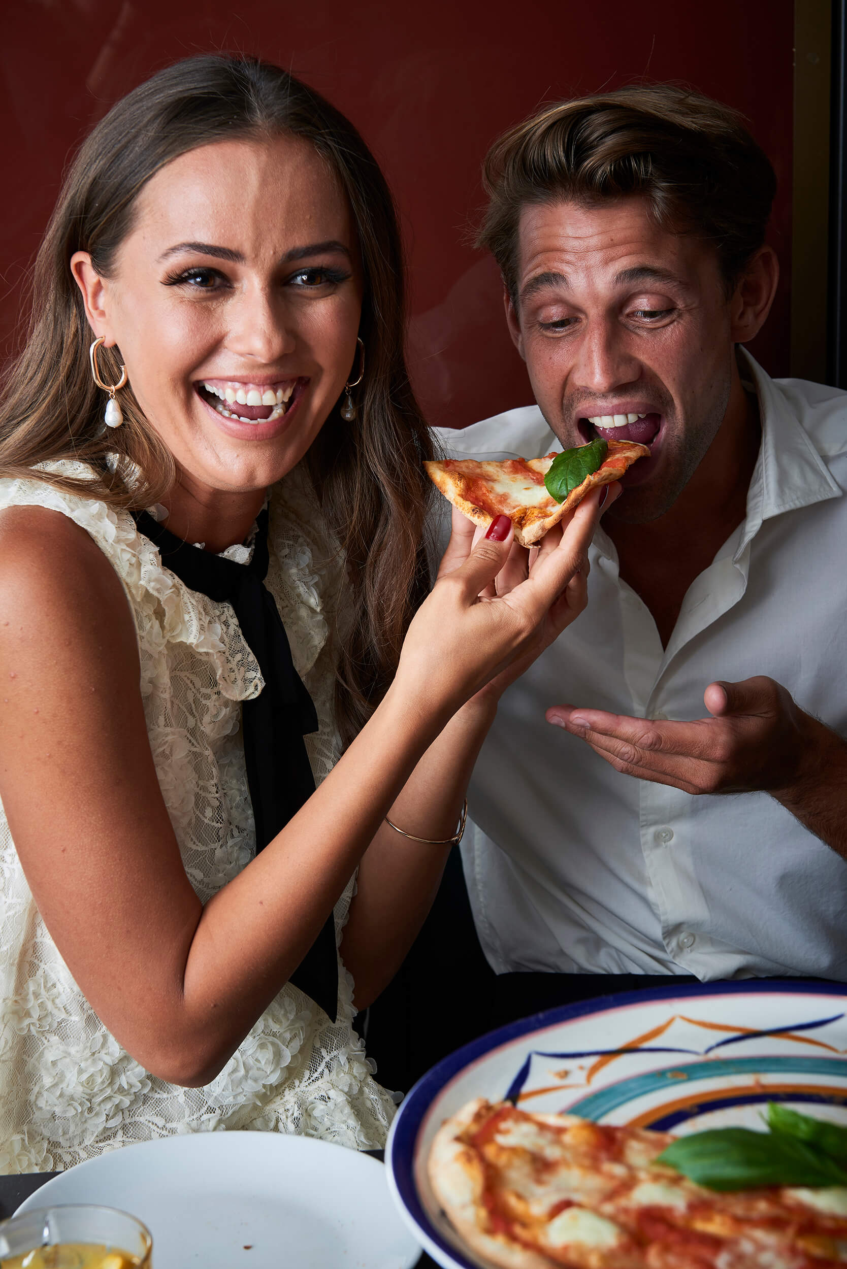 A woman offering a man a bite of pizza.