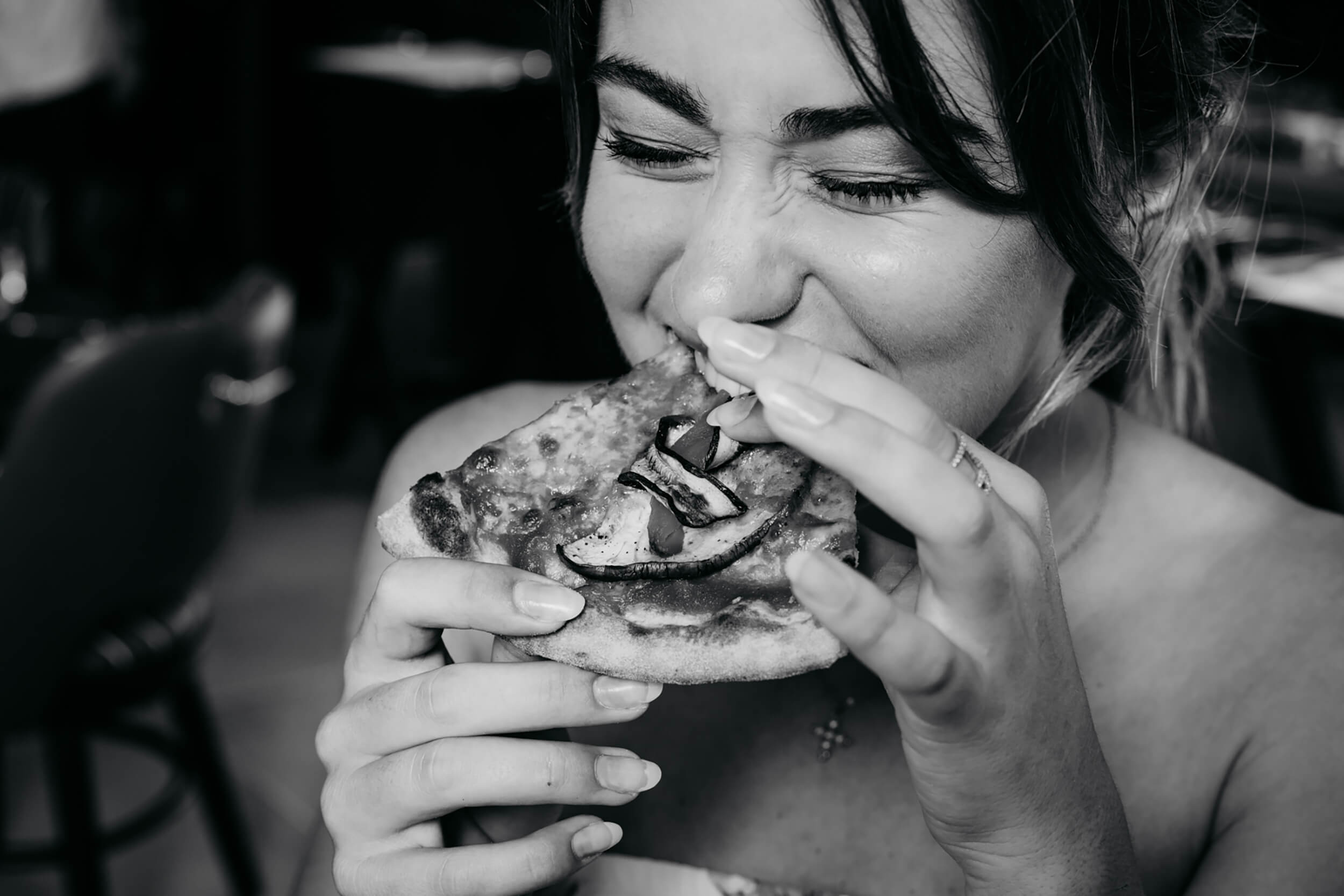 Woman taking a bite out of a pizza. The image is black and white.