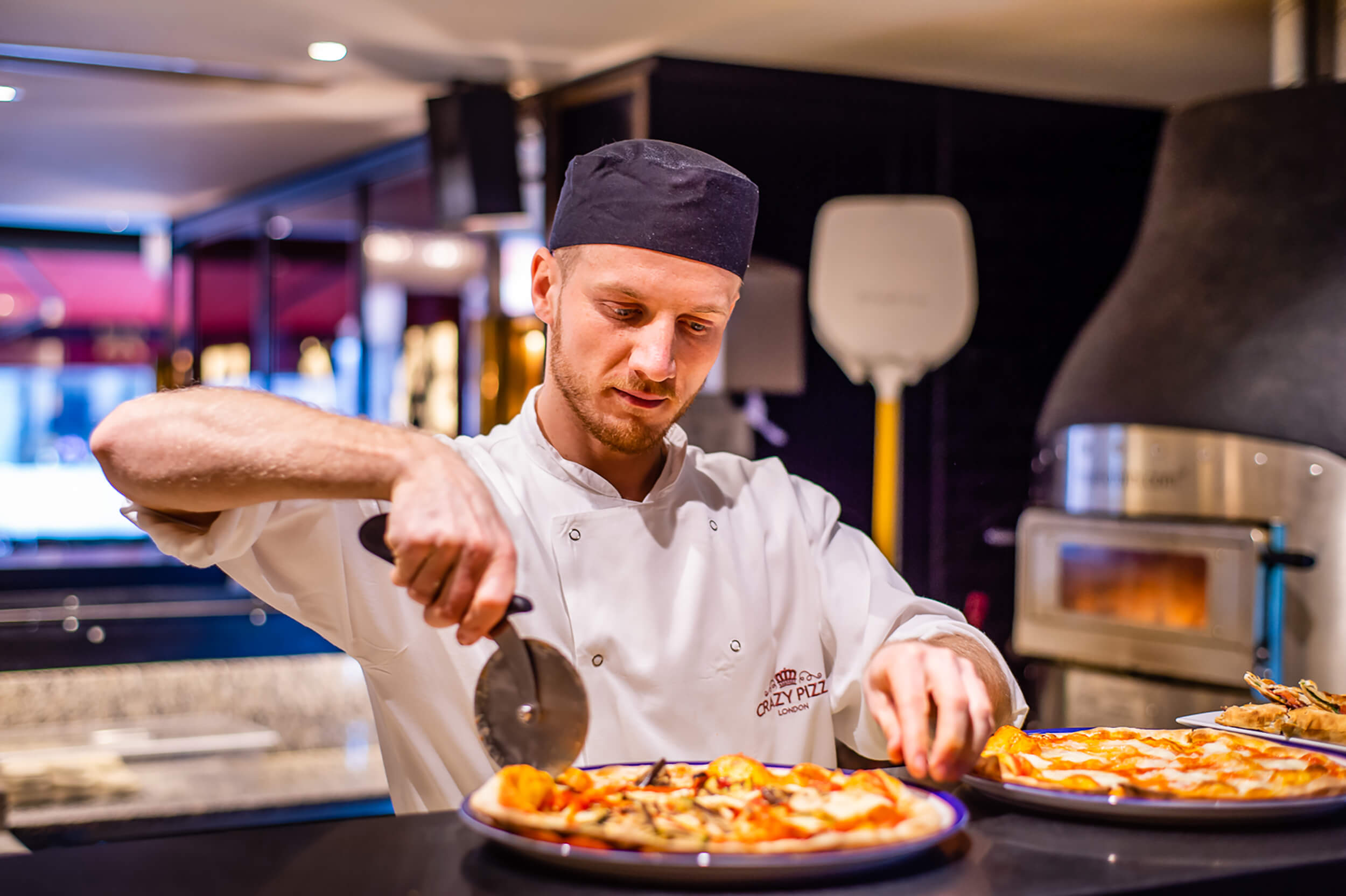 Chef cutting a pizza ready to be served.