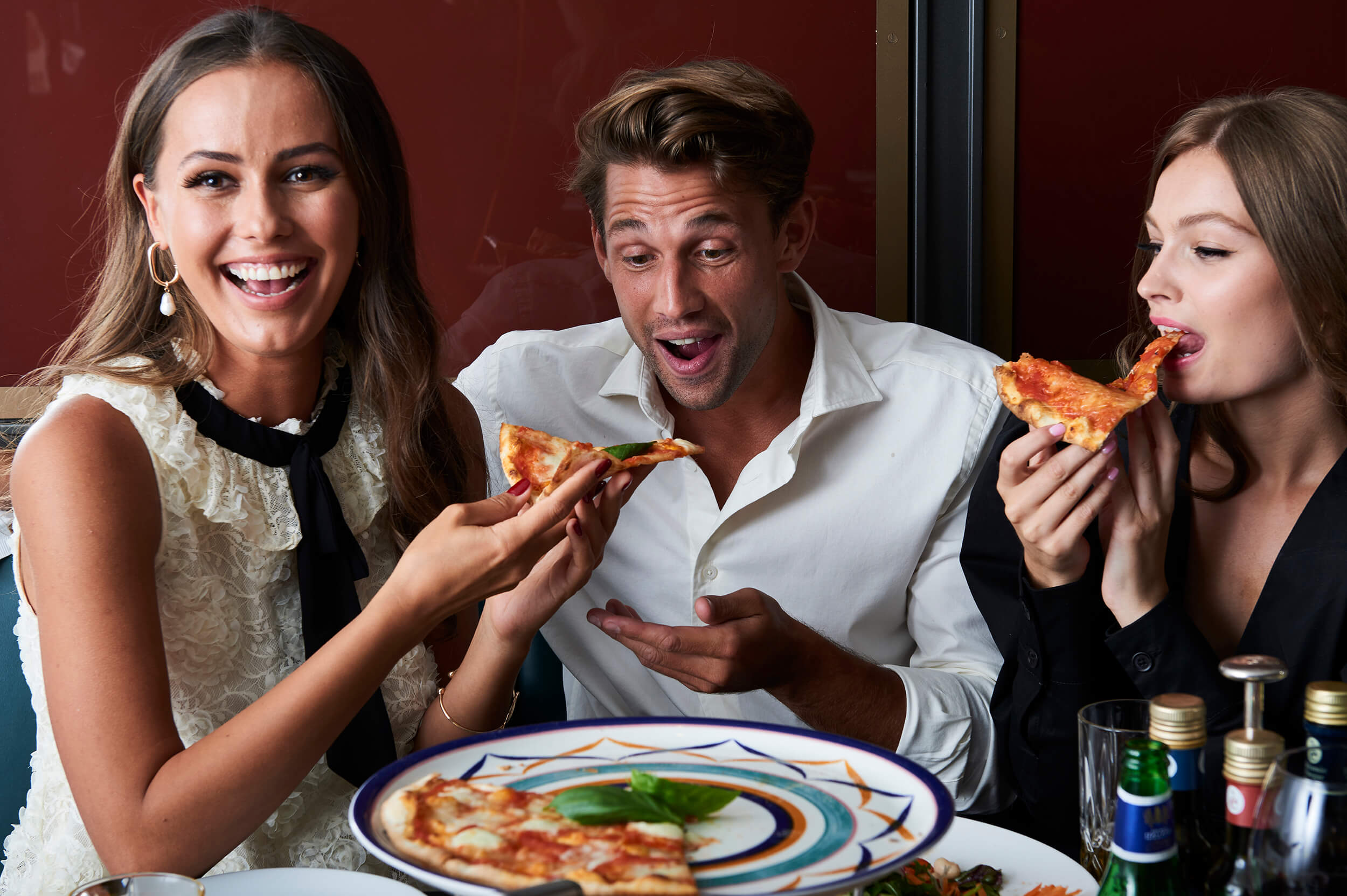 Two woman and a man enjoying pizza, laughing.