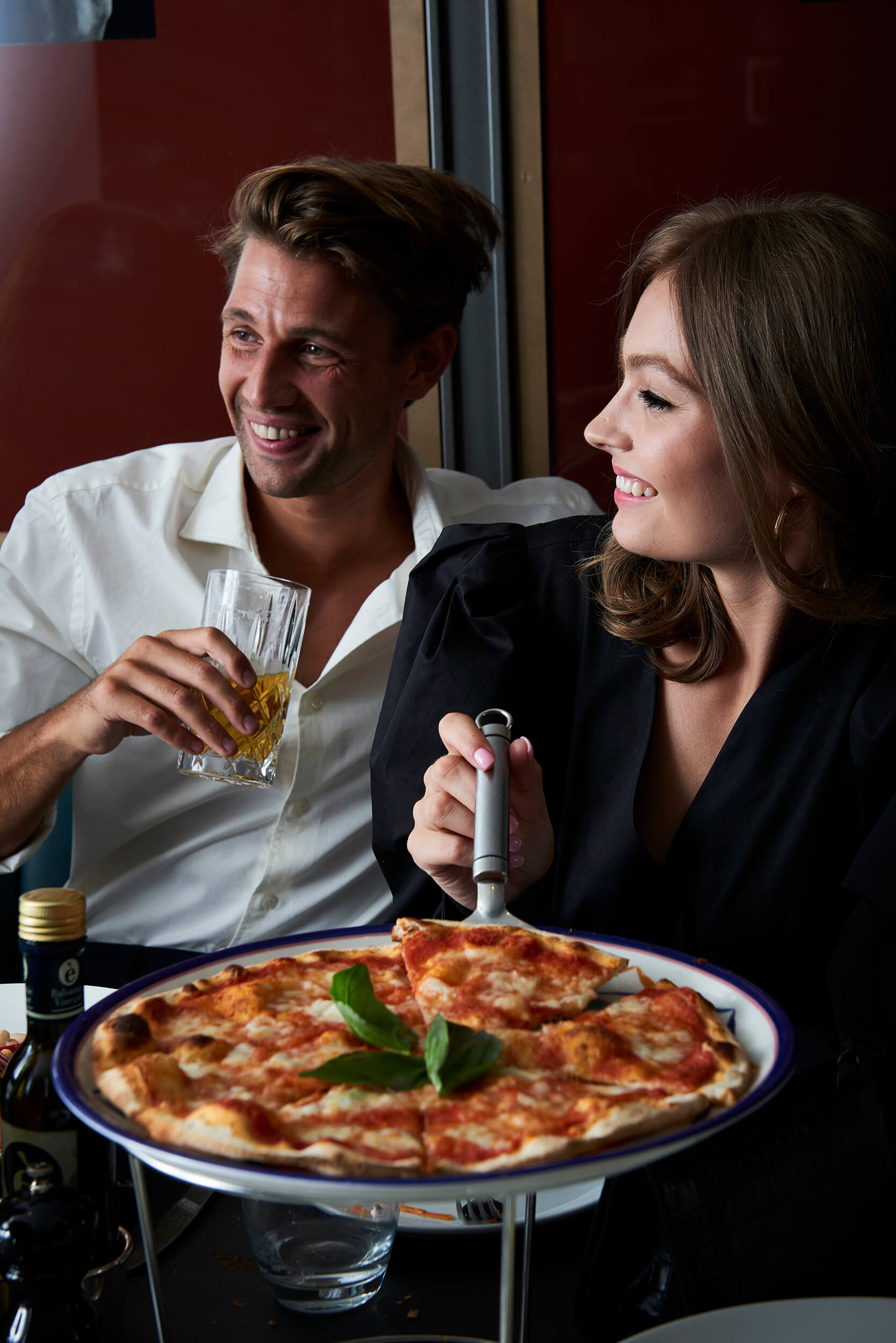 Couple eating pizza and drinking cocktails.
