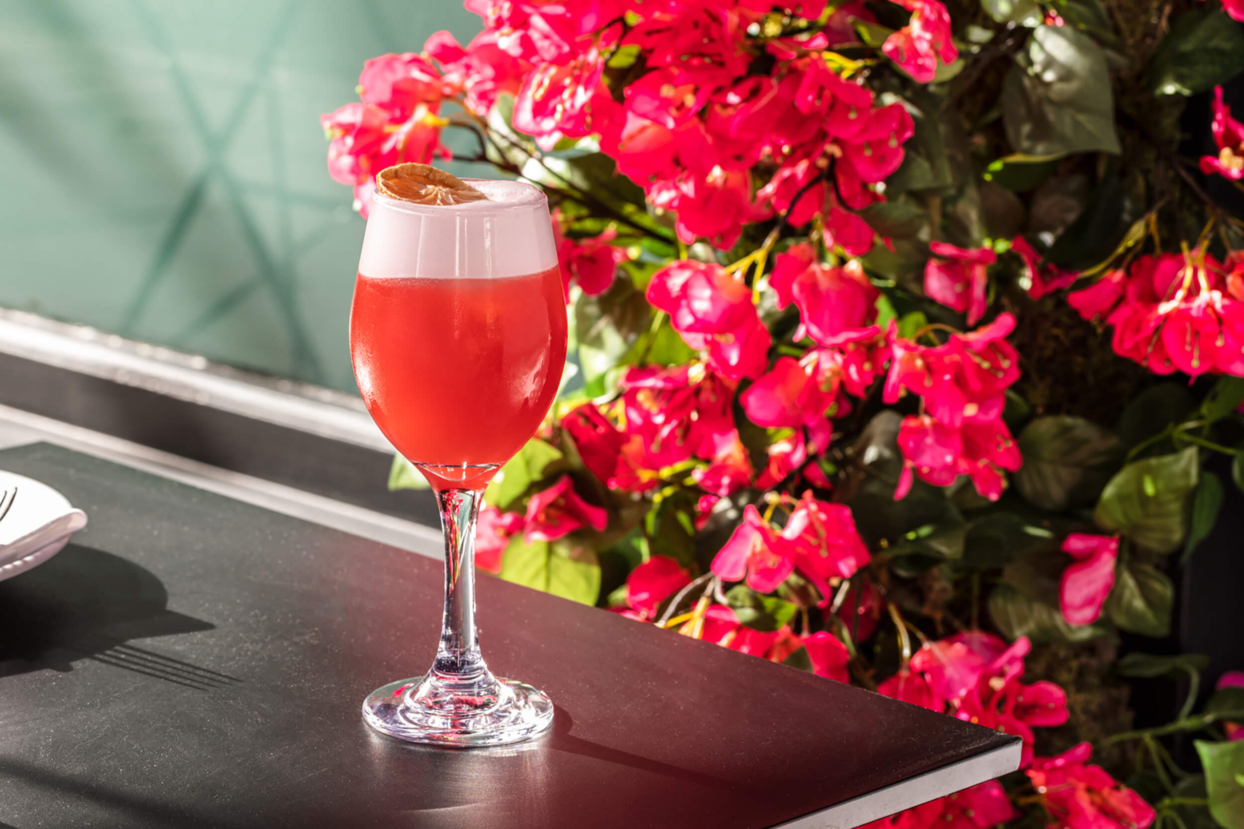 Pink cocktail in front of pink flowers.