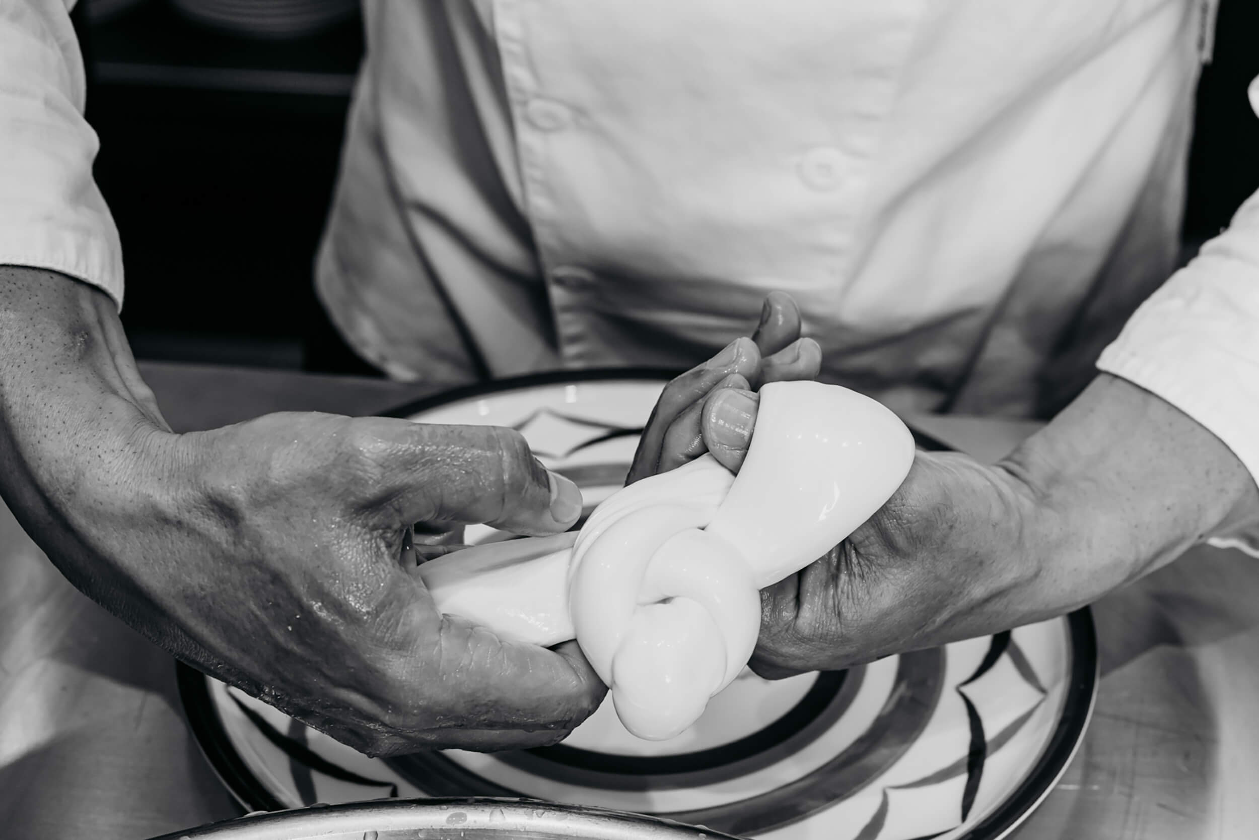Hands showing process of mozzarella making. The image is black and white.