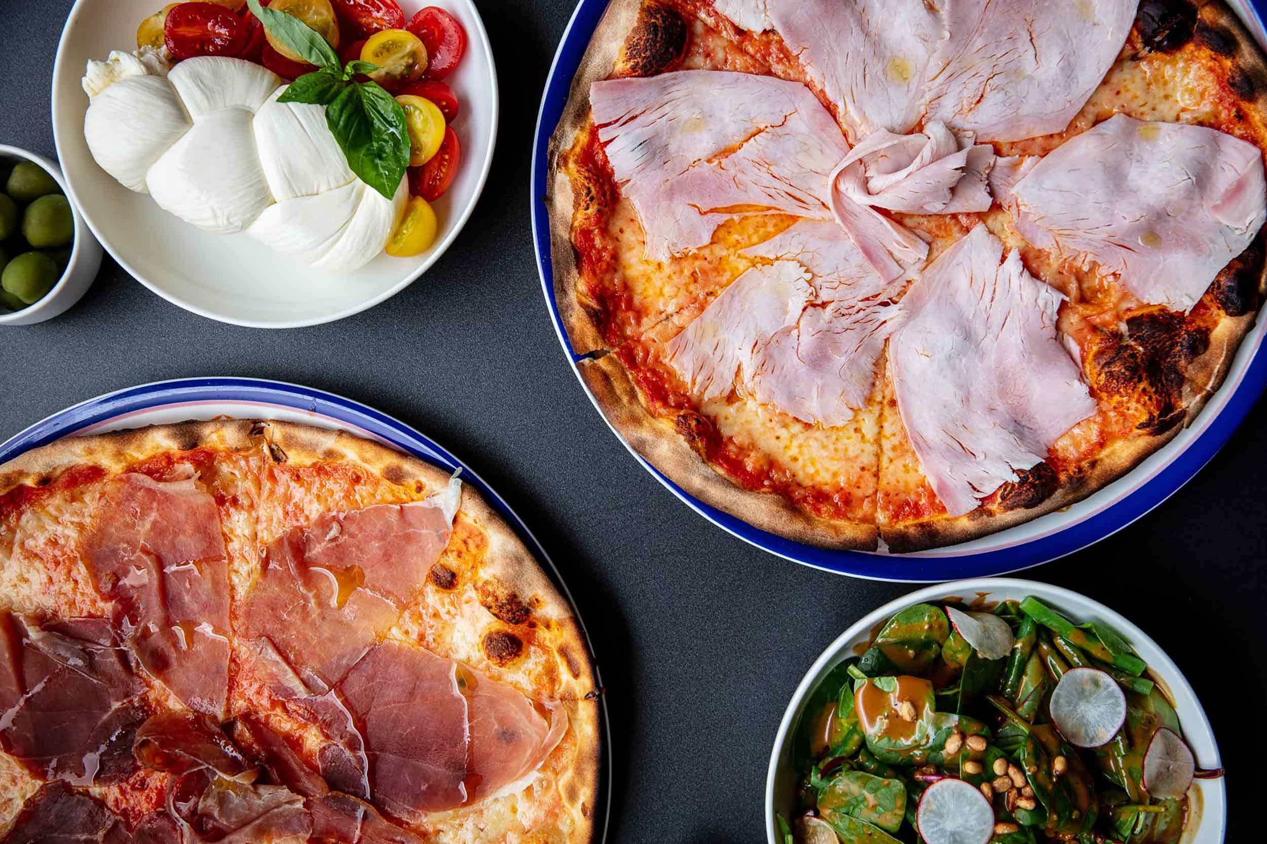 Top down view on pizzas and sides.