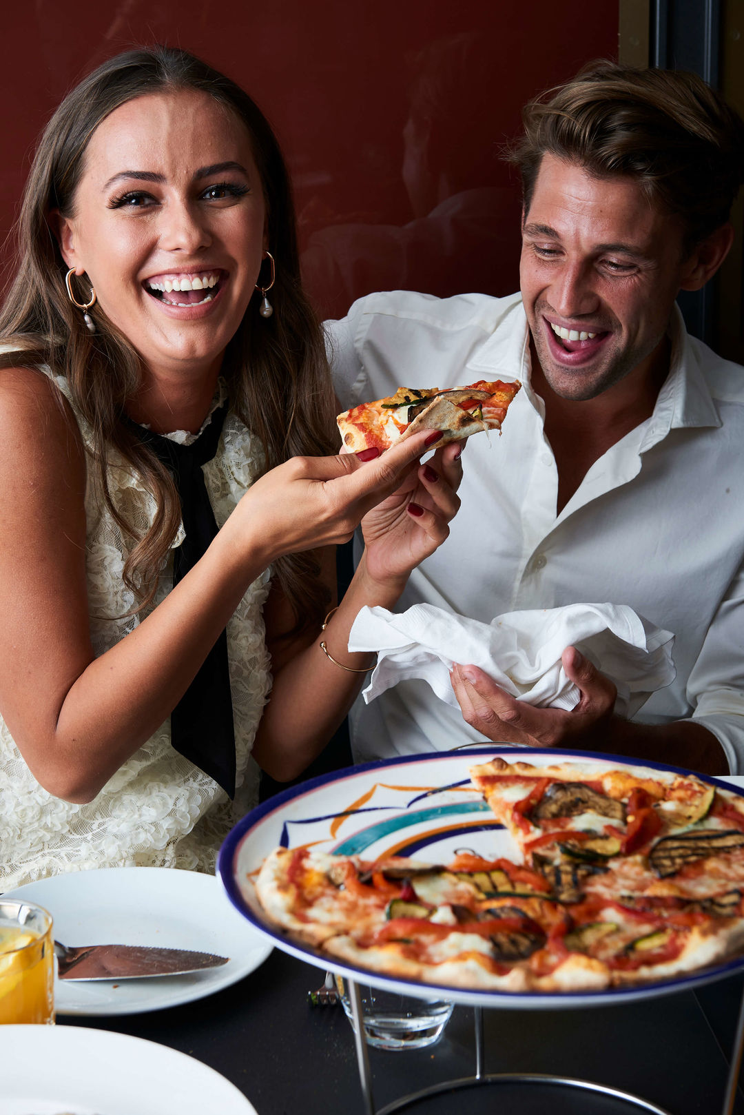 Couple taking a slice of pizza.
