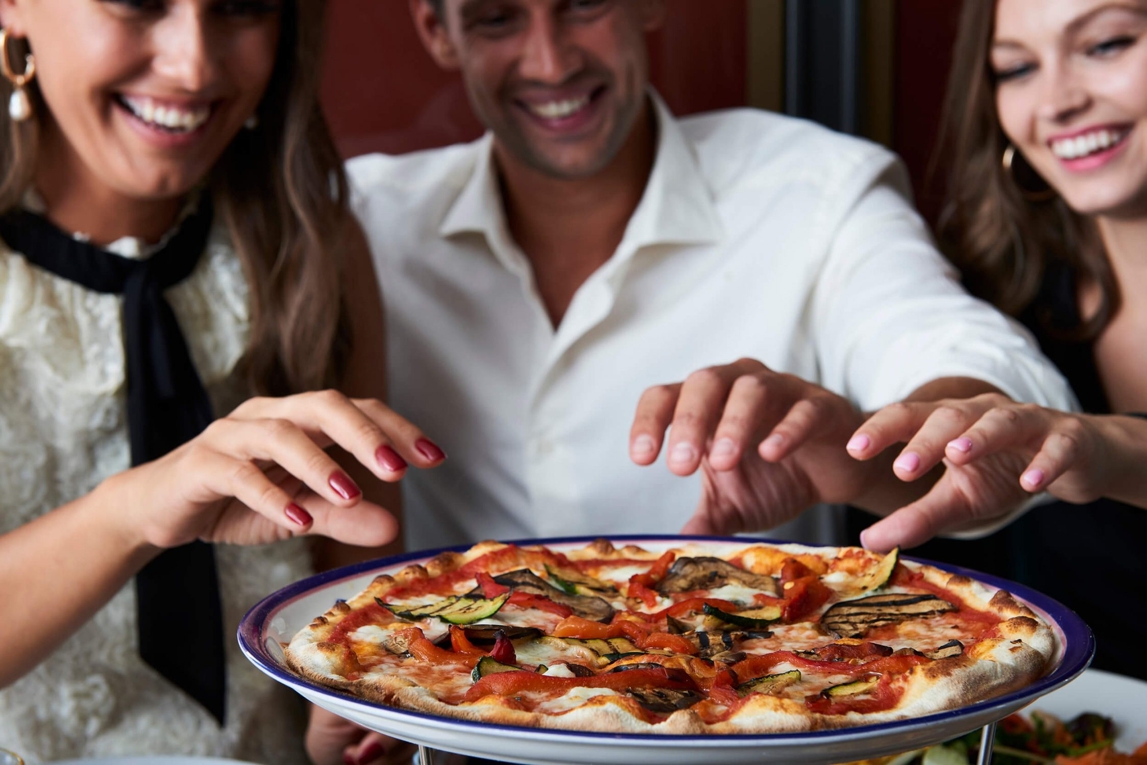 Two woman and a man simultaneously reaching for pizza.